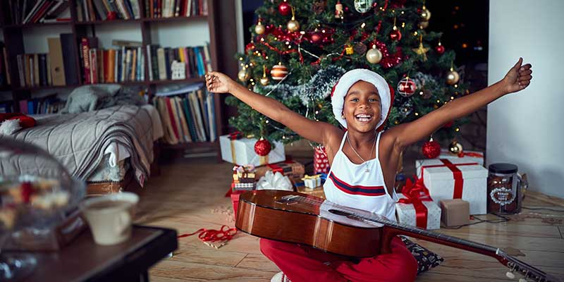 Little Boy Receives a Starter Guitar for Christmas